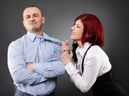 Geschäftsfrau zieht Geschäftsmann die Krawatte