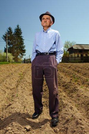 Photo pour Fermier âgé debout sur sa terre, sur le sol labouré - image libre de droit