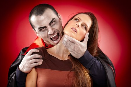 Vampire preparing to bite a beautiful woman's neck...