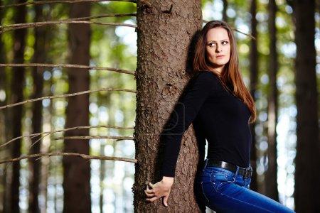 Photo pour Belle jeune femme appuyée sur un arbre dans une forêt - image libre de droit