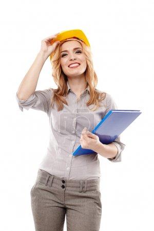 Photo pour Jeune ingénieure réussie portant un casque de protection et tenant un plan de construction, isolée sur fond blanc - image libre de droit