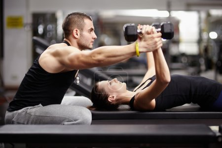 Photo for Personal trainer helping woman working with heavy dumbbells - Royalty Free Image