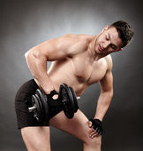 Athletic man working out with heavy dumbbells
