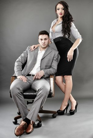 Sexy secretary and boss sitting on a chair