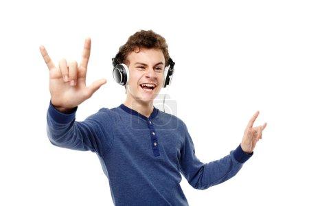 Photo pour Tournage en studio d'adolescents dansant, appréciant écouter de la musique au casque et faisant signe rock and roll, isolé sur fond blanc - image libre de droit