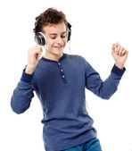 Teenager dancing and listening to music at headphones