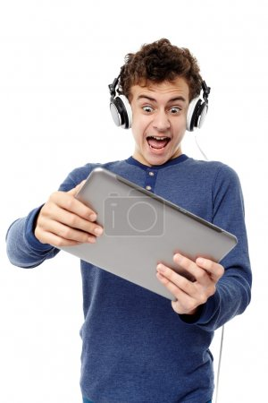 Teenager listening to music and screaming while looking at a tab