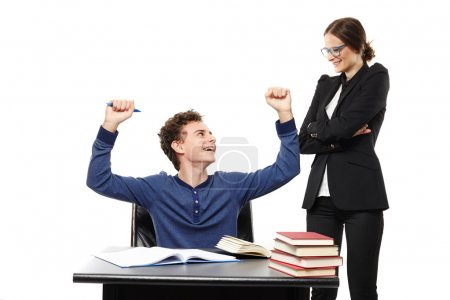 Student sitting at his desk looking happily at his teacher and throwing hands in the air