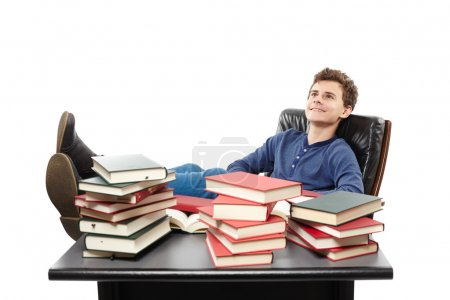 Photo for Studio shot of student having a rest with the legs on the desk, daydreaming among piles of books, isolated over white background - Royalty Free Image