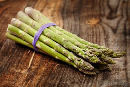Raw asparagus on wooden board
