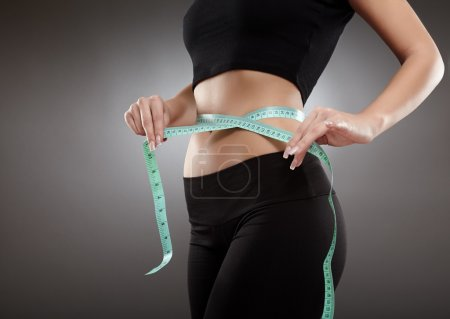 Photo for Closeup of a young and fit woman's waist with measuring tape - Royalty Free Image