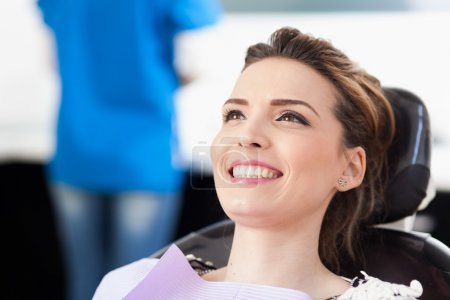 Photo for Closeup of a woman patient at the dentist waiting to be checked up with the woman doctor in the background - Royalty Free Image