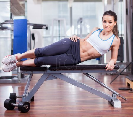 Athletic woman resting on a bench at the gym