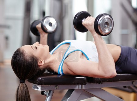 Woman working triceps and chest with dumbbells