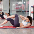 Young woman doing abs workout in a gym on a mat...