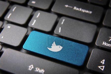 Photo pour Socialmedia clé avec icône oiseau twitter sur clavier d'ordinateur portable. tracé de détourage inclus, donc vous pouvez facilement le modifier. - image libre de droit