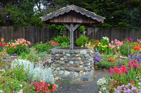 Old brick wishing well in colorful dahlia garden...