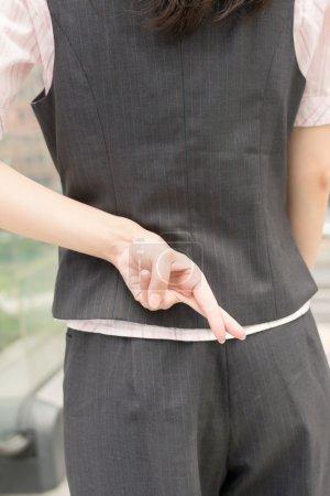 Photo pour Femme d'affaires croix doigt et mettre sur le dos, mensonge concept . - image libre de droit