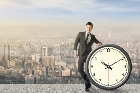 Photo for Asian businessman standing with a clock, concept of time manage or plan. - Royalty Free Image