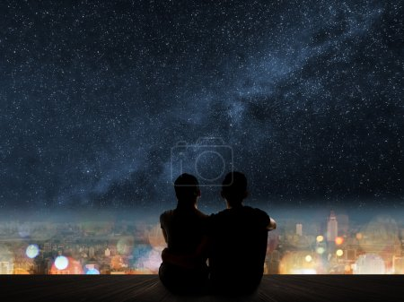 Photo for Silhouette of young Asian couple sit on wooden ground above the city under stars. - Royalty Free Image