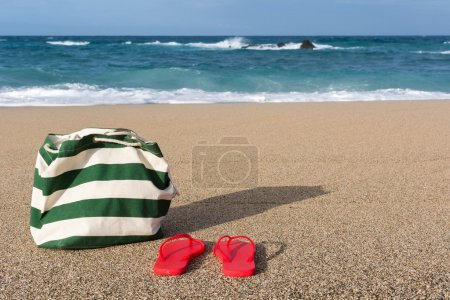 Photo for Summer concept of bag and flip flops on a tropical beach. - Royalty Free Image