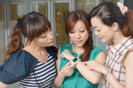 Photo pour Femme asiatique utilisant montre portable et montrant à ses amis . - image libre de droit