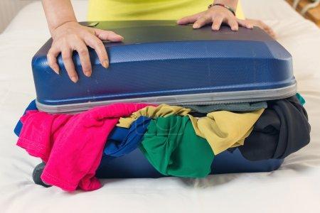 Photo pour Jeune femme essayer de fermer la valise surremplie dans la chambre . - image libre de droit