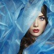 Fashion photo of beautiful women under blue veil. ...