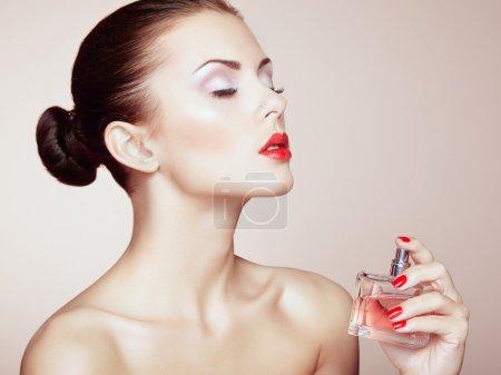 Photo pour Belle jeune femme avec une bouteille de parfum. maquillage parfait. photo de mode - image libre de droit