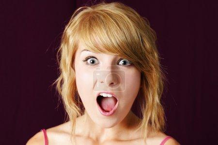 Photo pour Très surpris ou choqué jeune adolescent blond fille faisant la grimace, avec les yeux et la bouche grande ouverte, studio tourné. - image libre de droit