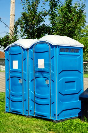 Photo for Two portable toilet or loo in blue plastic at a park public event or concert, with white sign on door ready for text. - Royalty Free Image