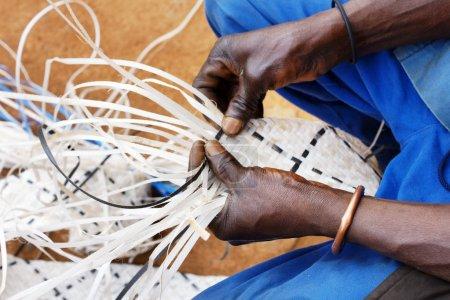 Man weaving long plastic strands