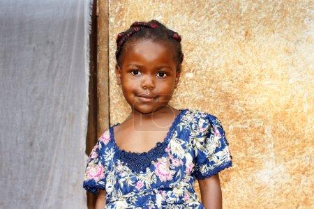 Foto de Retrato de una linda y dulce negra africana niña sonriente pero mirando un poco tímido, posando delante de su casa. - Imagen libre de derechos
