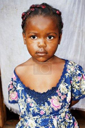 Foto de Retrato de una linda y dulce negra africana niña sonriente pero mirando un poco tímido, posando delante de su casa, grandes detalles. - Imagen libre de derechos