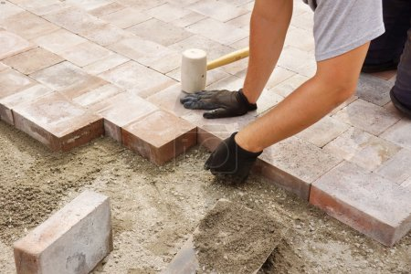 Worker installing paver