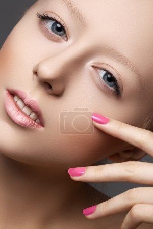 Beautiful young model with natural make-up and bright pink manicure. Wellness. Close-up beauty portrait of lovely european woman with clean healthy skin, pale lips, vibrance nail polish. Spa look