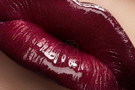 Photo for Close-up of woman's lips with bright fashion dark red glossy makeup. Macro lipgloss cherry make-up. Sexy kiss. - Royalty Free Image