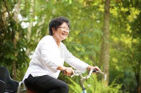 Photo for 60s senior Asian woman riding on bicycle outdoor with great fun - Royalty Free Image