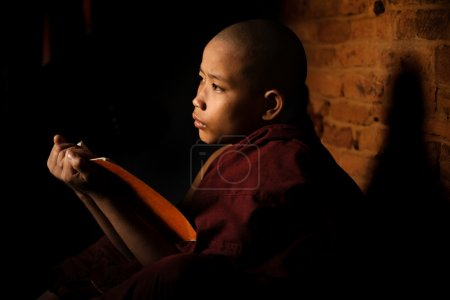 Photo for Young novice monk learning inside monastery - Royalty Free Image