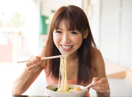 Photo for Portrait of happy smiling young Asian woman eating Asian noodles - Royalty Free Image