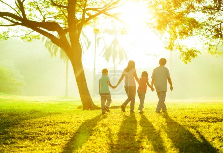 Photo for Happy Asian family holding hands walking over green lawn - Royalty Free Image