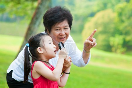 Photo for Asian grandmother and granddaughter exploring nature by magnifier - Royalty Free Image