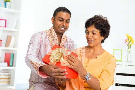Photo for Mature Indian woman receiving a gift from her son - Royalty Free Image