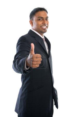 Foto de Pulgar emocionado hasta 30 años empresario indio en traje negro aislado sobre fondo blanco - Imagen libre de derechos