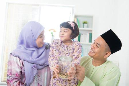 Photo pour Famille sud-est asiatique. musulmane main tenant pot d'argent à la maison . - image libre de droit