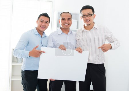 Southeast Asian business team holding a blank bann...