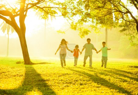 Photo for Southeast Asian Chinese family holding hands, running at outdoor green park during sunrise - Royalty Free Image