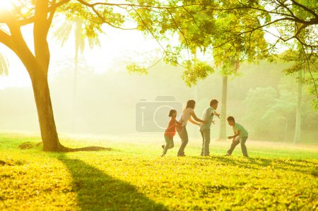 Photo for Asian family outdoor quality time enjoyment, asian playing during beautiful sunrise - Royalty Free Image