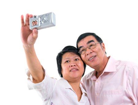 Asian senior couple self photographing