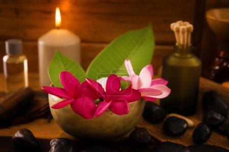Photo pour Réglage de la Spa avec fleur de frangipanier, huiles essentielles, pierres zen et des bougies aromatiques sur table, concept zen. - image libre de droit